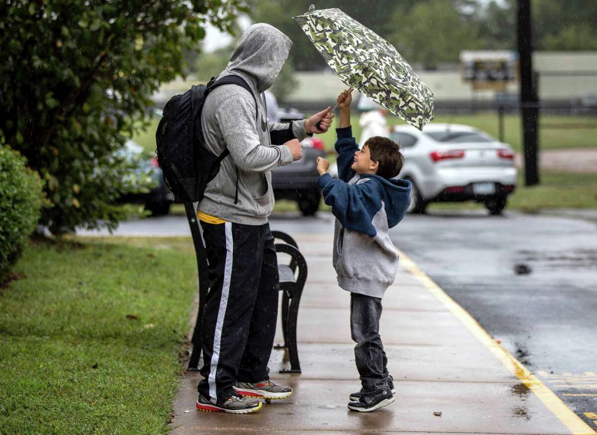 Kindergartener Jovanni Aranda, 6, right, shares his umbrella with physical education teacher Chase Davidson as he waits in Colonial Beach, Va., to be picked up after school on Friday, Oct. 2, 2015. Colonial Beach Elementary School dismissed early due to rains from impending Hurricane Joaquin. (Sarah Ann Jump/The Free Lance-Star via AP) MANDATORY CREDIT