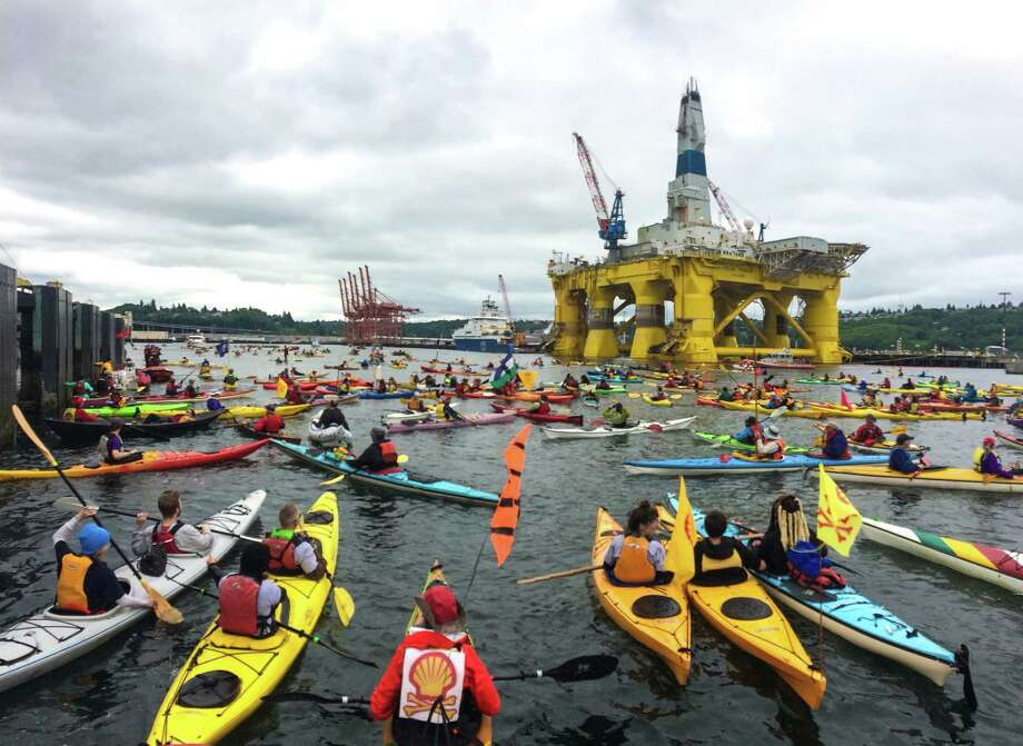 """In May, self-proclaimed """"kayaktavists"""" took to Seattle waters to protest Shell's Arctic quest, while the Transocean Polar Pioneer drilling rig, on its way to the Arctic, towered over them. Photo: Joshua Trujillo, MBO / seattlepi.com"""