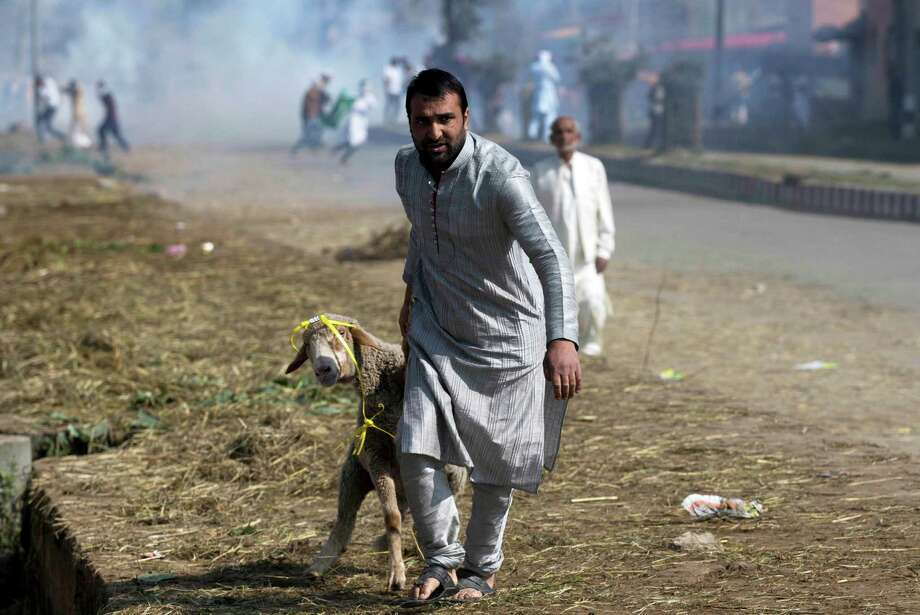 A Kashmiri man leads a goat past protestors after Eid al-Adha prayers in Srinagar, Indian controlled Kashmir, Friday, Sept. 25, 2015. Police fired teargas and rubber bullets to disperse hundreds of Kashmiris protesting a court ruling upholding a colonial-era law banning cow slaughter and the sale of beef in the Indian-controlled portion of Kashmir. (AP Photo/Dar Yasin) Photo: Dar Yasin, STF / Associated Press / AP