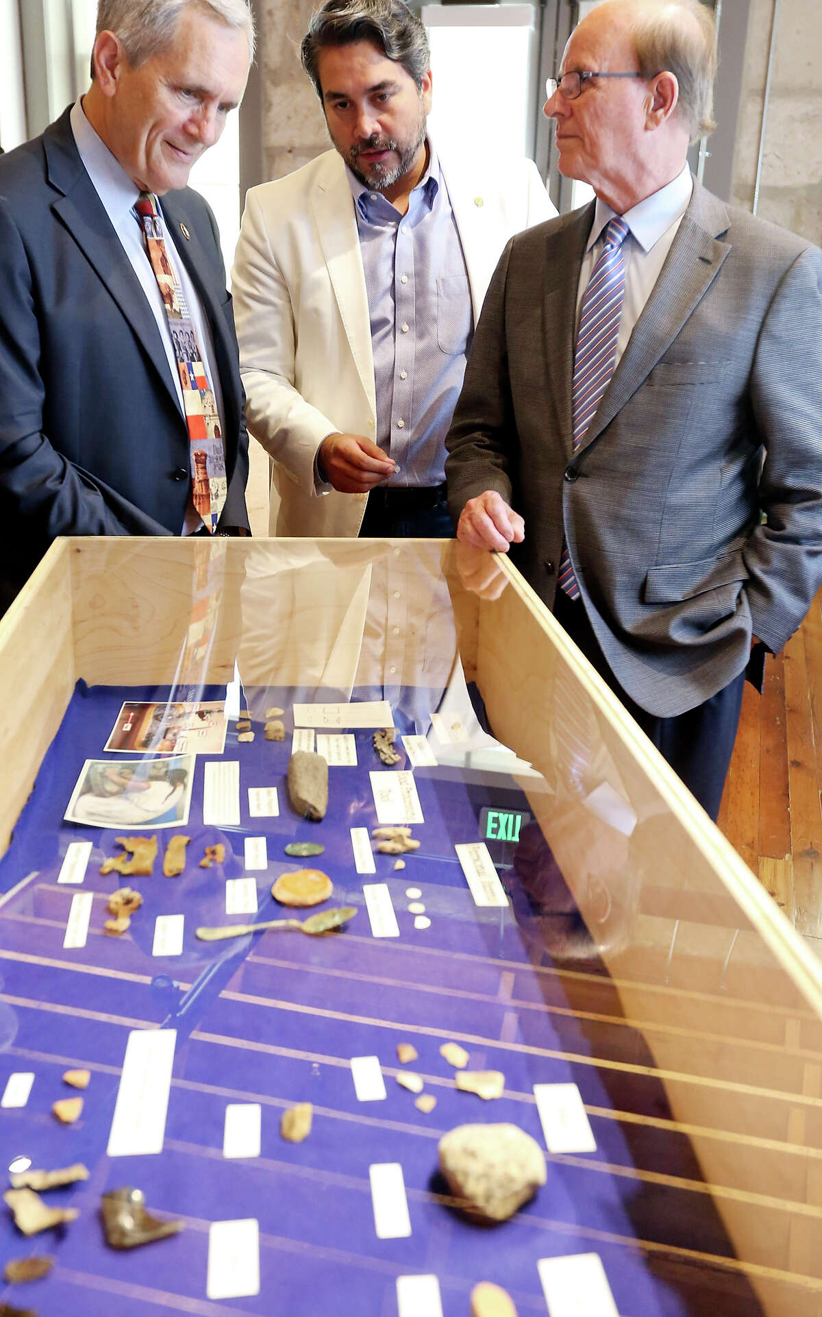 U.S. Rep. Lloyd Doggett (from left), District 1 Councilman Robert Trevino, and Bexar County Judge Nelson Wolff look at artifacts from the probable first site of the Mission San Antonio de Valero (1718) after a press conference held Friday Oct. 2, 2015 in the Culture Commons Storefront Gallery & Exhibit Hall at the Plaza de Armas Building.