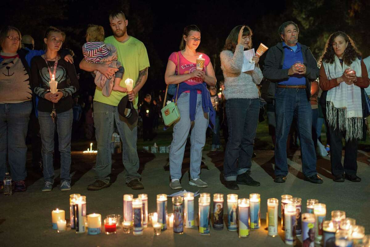 People pray during a candlelight vigil in Roseburg, Oregon late on Thursday.