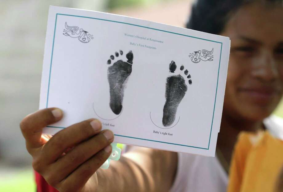 An undocumented woman in Sullivan City shows the footprints of her daughter born in the United States but denied a birth certificate. Texas argues that certain Mexican documents do not meet identity standards, but lawyers for the immigrants say it's the only state with such rules. Photo: Eric Gay, STF / AP
