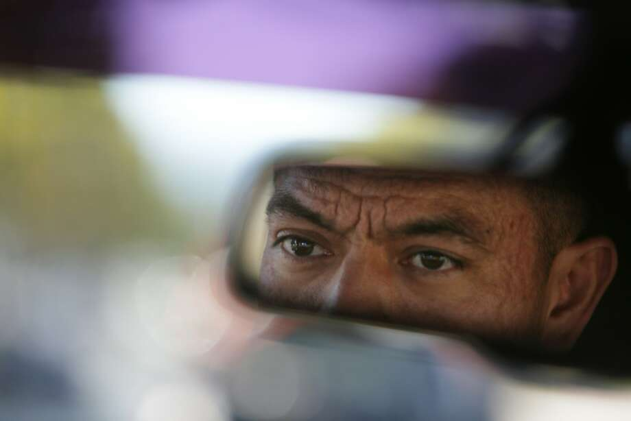 Alcaraz's face is reflected in his rearview mirror as he patrols neighborhoods in East Palo Alto. Photo: Lea Suzuki, The Chronicle