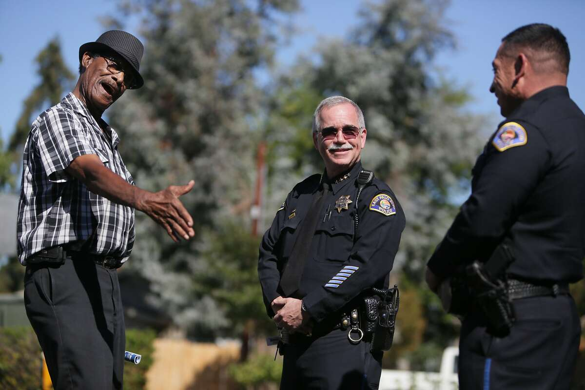 Dempsey Mitchell, East Palo Alto senior center driver, holds his hand out to shake that of East Palo Alto police commander Jerry Alcaraz (right) while talking with East Palo Alto police chief Al Pardini (center) in front of the East Palo Alto Senior Center on Friday, October 2, 2015 in East Palo Alto, Calif.