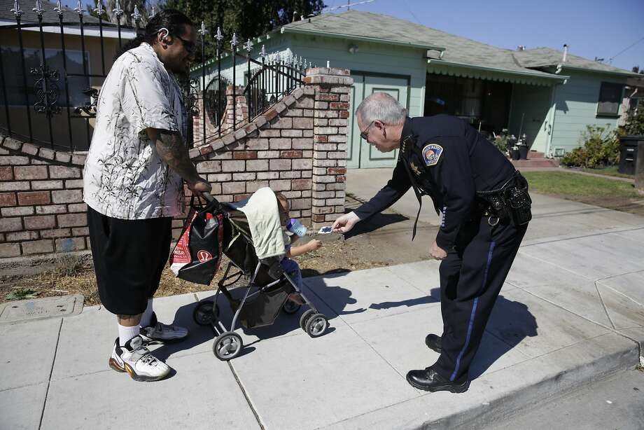 While on his regular foot patrol, East Palo Alto Police Chief Albert Pardini stops to chat with 1½-year-old Taufa Makasini and his father, Kevin Makasini. Photo: Lea Suzuki, The Chronicle