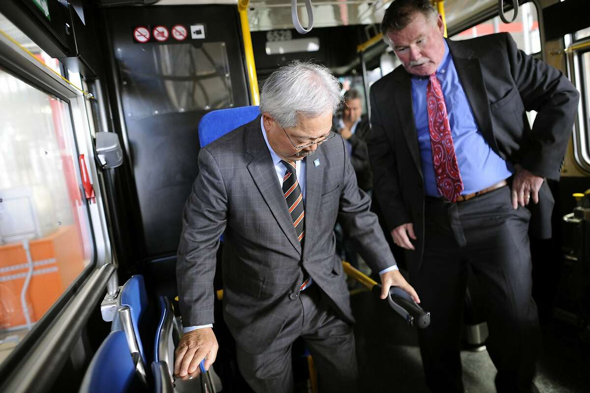 SMFTA director of transit operations John Haley, right, explains to Mayor Ed Lee how the new handicap seats work on a new MUNI bus during a press conference announcing MUNI service improvements, in San Francisco, CA Monday, September 28, 2015.