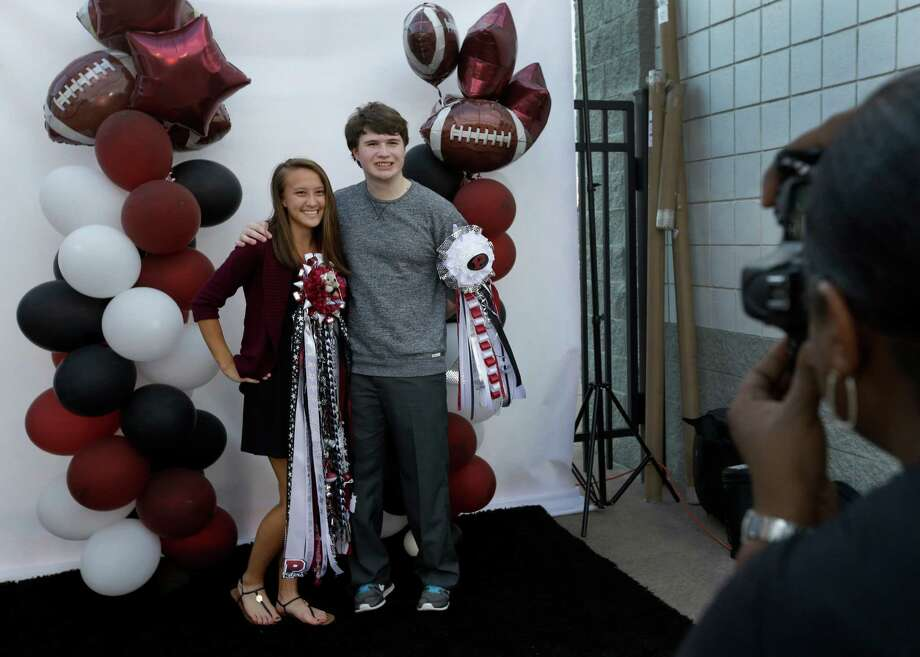 Sarah Howe and Mitchell Jackson, juniors at Pearland High School, have their photo taken at a fund-raising booth at the recent homecoming game, but the school canceled its homecoming dance. Photo: Melissa Phillip, Staff / © 2015 Houston Chronicle