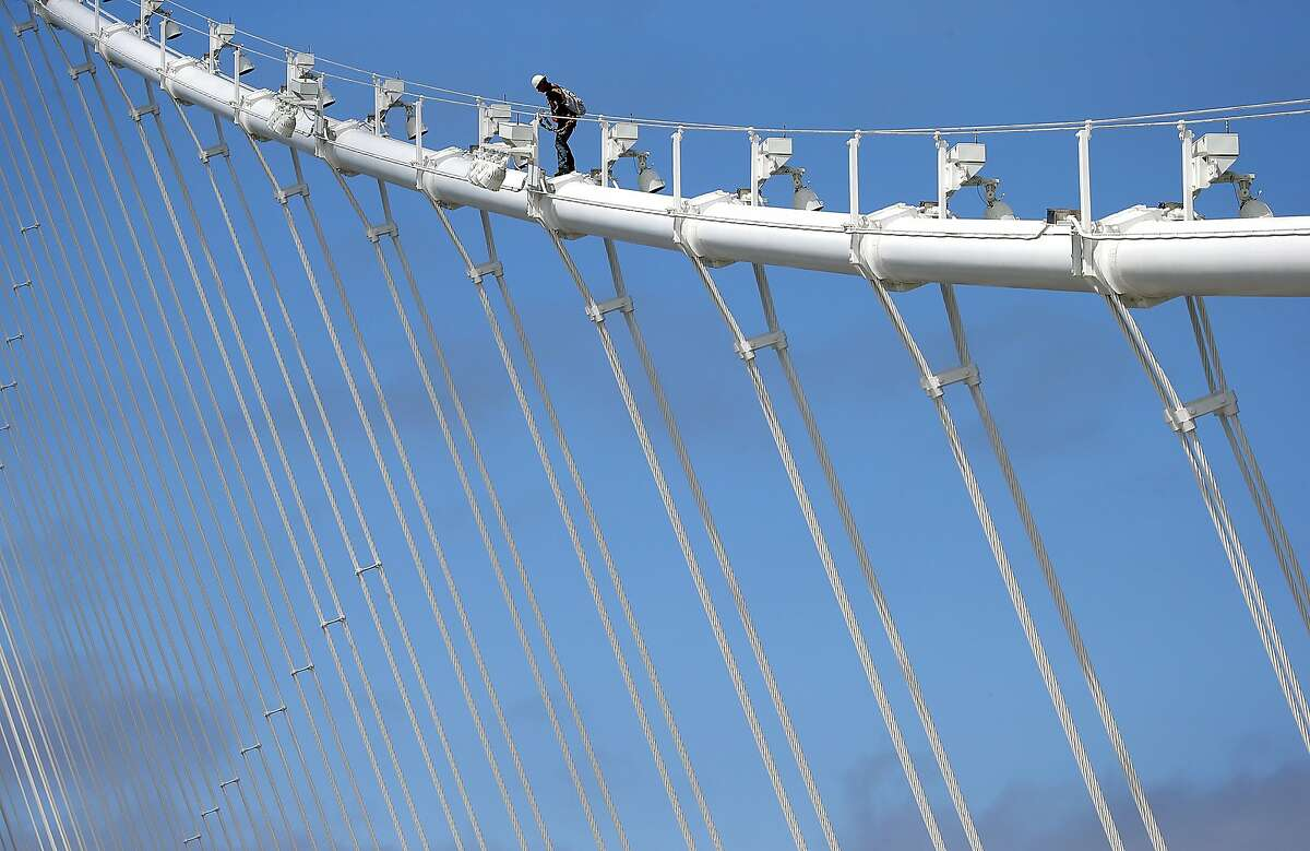 OAKLAND, CA - JULY 12: A bridge worker walks up a cable of the newly constructed San Francisco-Oakland Bay Bridge on July 12, 2013 in Oakland, California. Workers began paving the roadway of the newly constructed east span of the San Francisco-Oakland Bay Bridge just days after bridge officials announced that the opening of the span would be delayed once again as work continues to install large steel saddles over two seismic safety devices to fix a problem with broken bolts on two shear keys. The bridge has been under construction since 2002 with an estimated price tag of $6.3 billion and will have the world's tallest Self-Anchored Suspension (SAS) tower once completed. (Photo by Justin Sullivan/Getty Images) *** BESTPIX ***