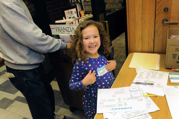 Six-year-old Sadie Leon of Scotia joins other volunteers set up 40,000 books for sale during the Friends of the Schenectady County Public Library's annual fall used book sale at Schenectady Public Library on Friday, Oct. 2, 2015, in Schenectady , N.Y. The sale takes place at  9 a.m. to 4 p.m. Saturday in and outside the library at 99 Clinton Street.   (Michael P. Farrell/Times Union) Photo: Michael P. Farrell / 00033510A