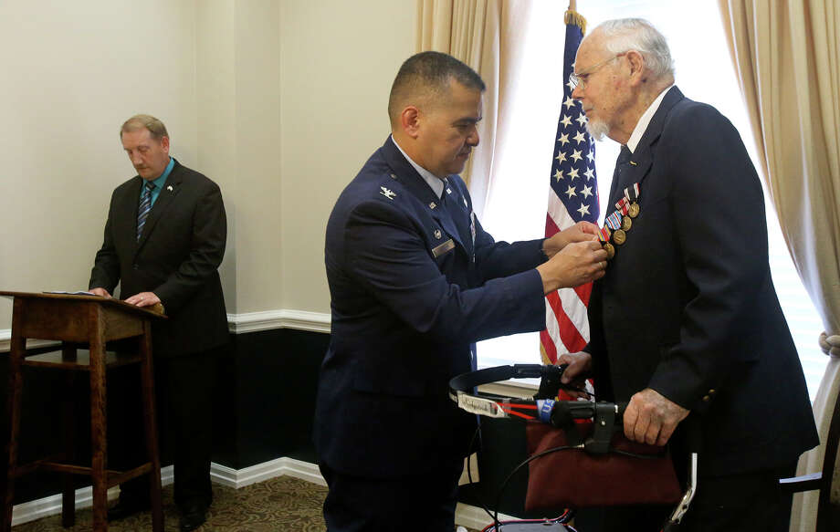 "U.S. Air Force Colonel Richard Lindlan (center) pins medals Friday October 2, 2015 on World War II veteran Wallace B. Kirkpatrick,94, (right) for his service. Kirkpatrick was a prisoner of war and was part of a group known as ""Penguins"" that helped POWs tunnel their way out of prison camps much like in the movie ""The Great Escape."" Kirkpatrick received the Prisoner of War medal, the Good Conduct medal with three bronze loops, the American Campaign medal, the World War II Victory medal and the National Defense medal. On the left is Will Brown, the Chief of the Air Force Evaluation and Recognition Programs Branch. Photo: John Davenport /San Antonio Express-News / ©San Antonio Express-News/John Davenport"