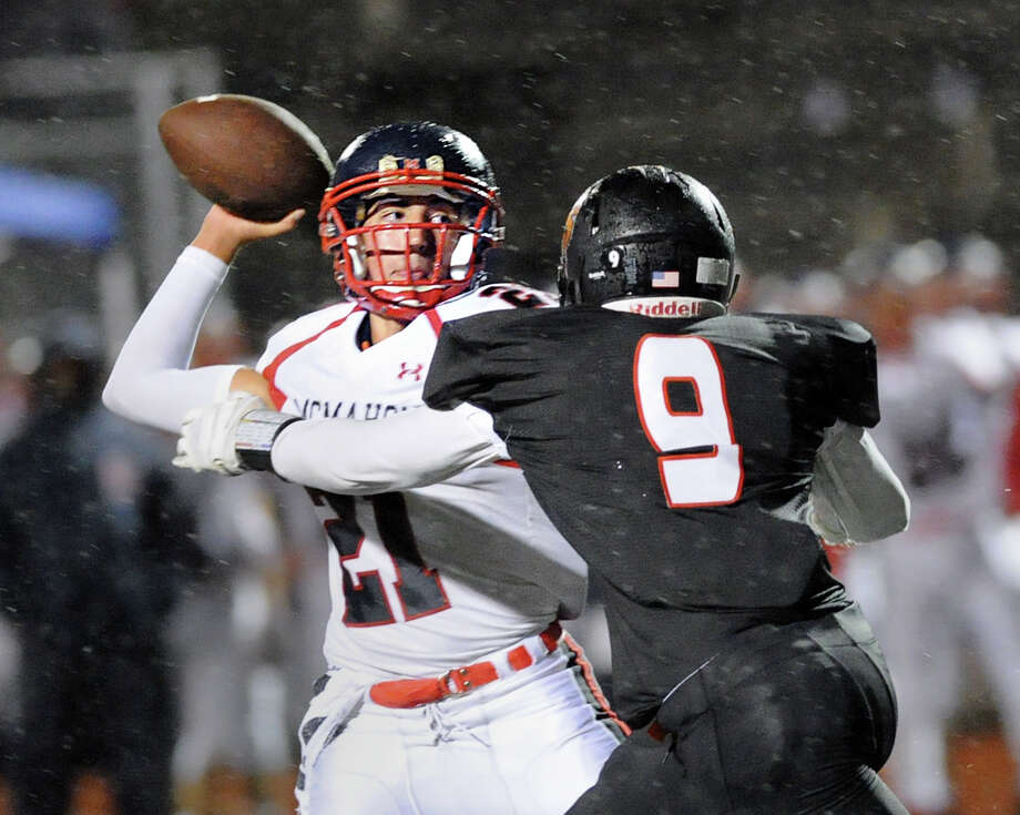 Brien McMahon quarterback Chris Druin, left, is pressured by Stamford's Ben Joseph (9) Friday night. Photo: Bob Luckey Jr. / Hearst Connecticut Media / Greenwich Time