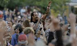 Michael Franti goes out into the crowd filled meadow for a few songs, play the Banjo Stage, during the first day of Hardly Strictly Bluegrass in Golden Gate Park on Fri. October 2, 2015,  in San Francisco, Calif.,