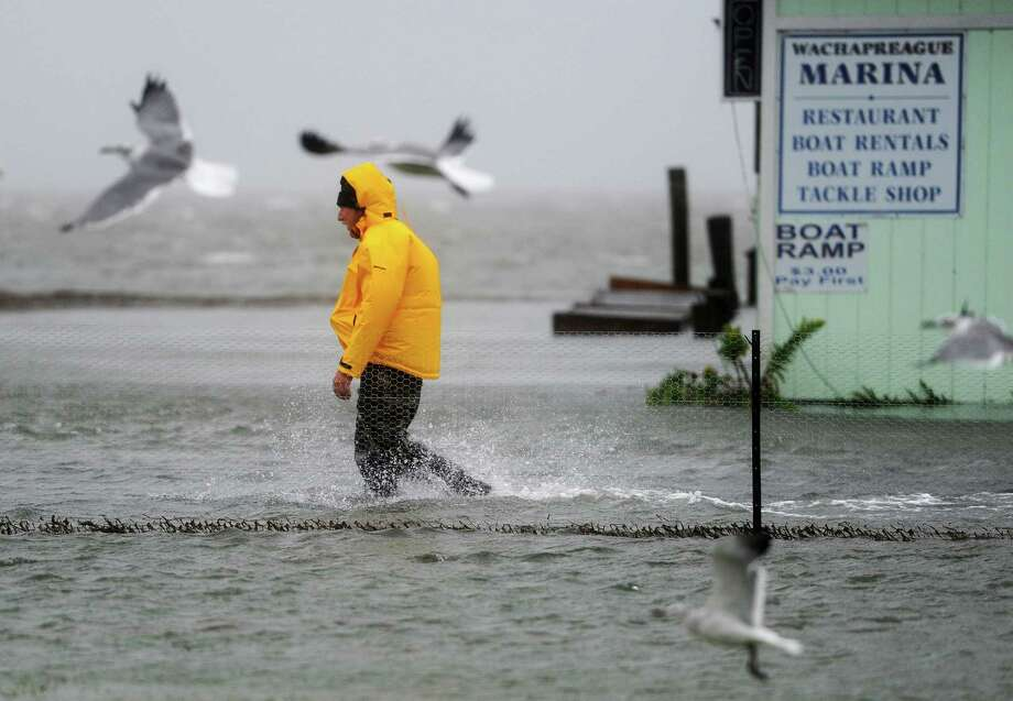 A man wades through flood water Friday in Wachapreague, Va., after a storm hit, but Hurricane Joaquin is now expected to turn away from the U.S. Photo: Jay Diem, MBO / The Daily Times