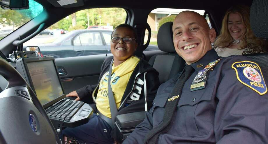 Messiah Hodge-Humphrey and Albany Police Officer Michael Geraci ride in a police car on the way to purchase new electronic equipment at Wal-Mart after the 13-year-old autistic boy's favorite possessions were stolen in a burglary at his house. (Photo courtesy of Albany Police Department)