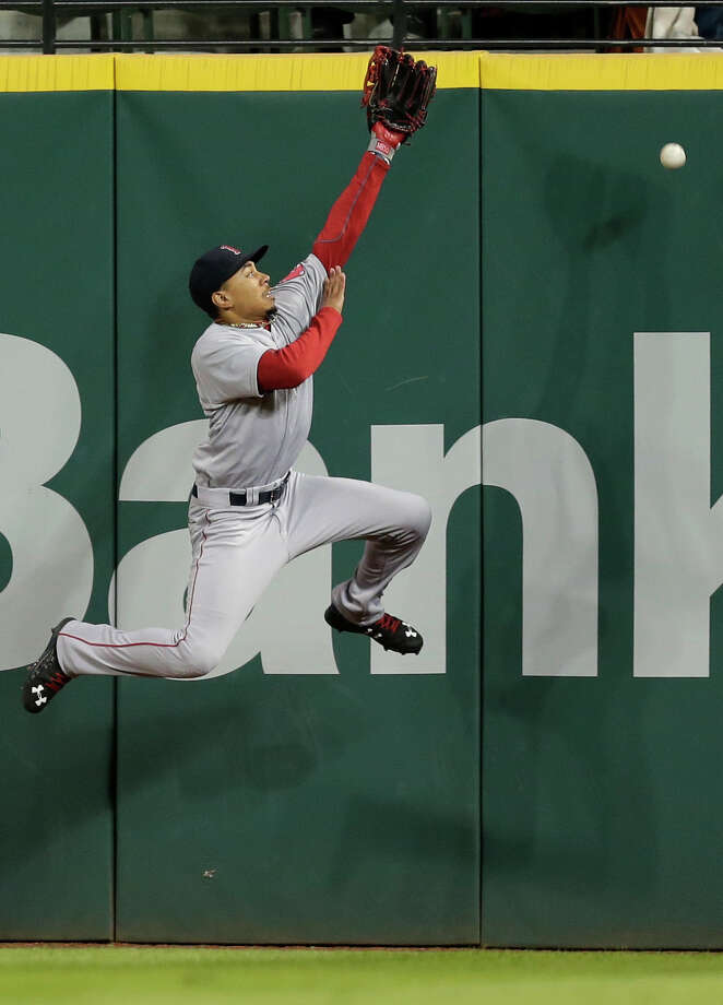 Boston Red Sox' Mookie Betts jumps but can't reach a ball hit for an RBI-double hit by Cleveland Indians' Yan Gomes in the fifth inning of a baseball game, Friday, Oct. 2, 2015, in Cleveland. Carlos Santana scored on the play. (AP Photo/Tony Dejak) ORG XMIT: OHTD109 Photo: Tony Dejak / AP