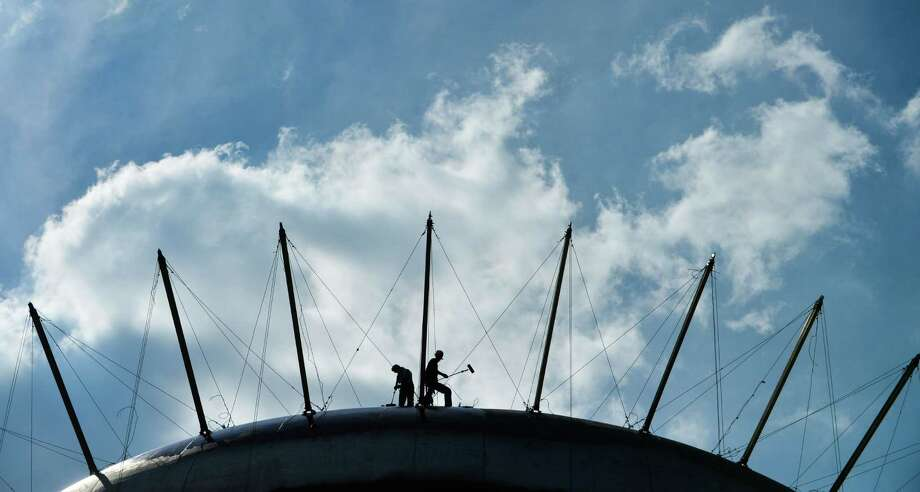 In this Sept. 15, 2015 photo, painters work on top of the water tank in Delano Park in Decatur, Ala. The U.S. government issues the September jobs report on Friday, Oct. 2, 2015. (Gary Cosby Jr./The Decatur Daily via AP) ORG XMIT: ALDEC301 Photo: Gary Cosby Jr. / The Decatur Daily