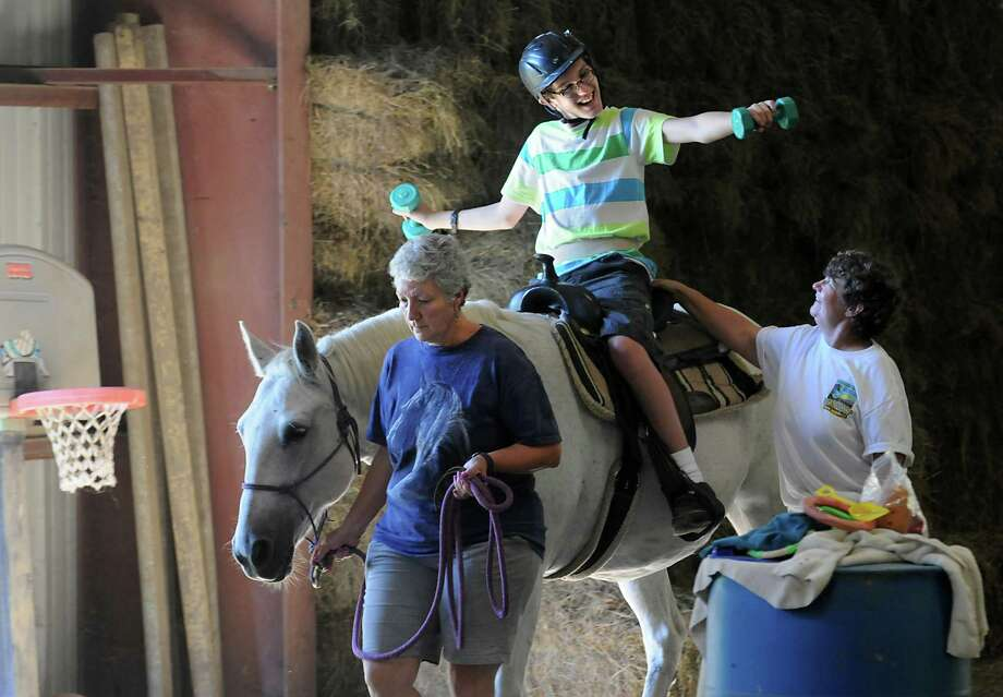 Britta Lovegrove, left, and Liz Chauvot walk with Trevor Bailey, 13, of Amsterdam who is riding Flint at EBC Therapy Center on Thursday, Sept. 17, 2015 in East Berne, N.Y. The women run the horse farm and provide equine therapy to children and adults. (Lori Van Buren / Times Union) Photo: Lori Van Buren / 00033393A