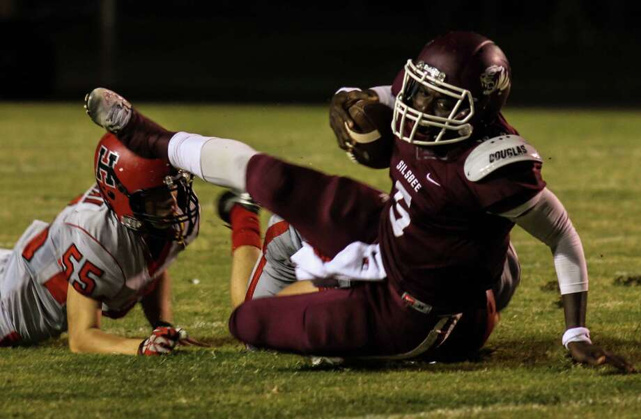 The Silsbee Tiger's Dontre' Thomas is tripped by the Huffman Falcon's Tyler Price  Friday Night at Tiger's Stadium by Denzel Seale.