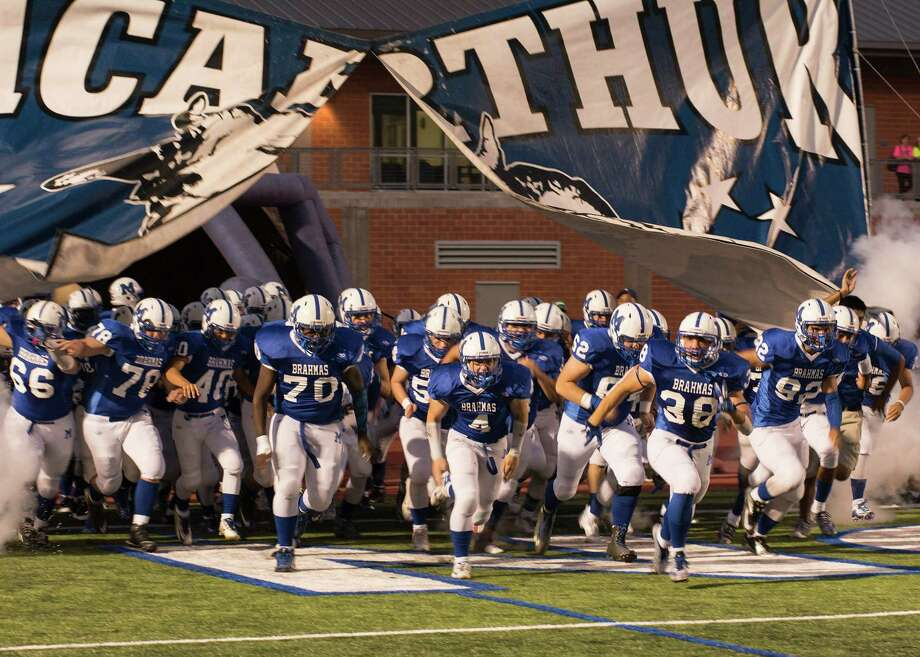 The MacArthur team charges out of the tunnel before their game against Churchill on Friday, Oct. 2, 2015. Photo: Jena Stopczynski
