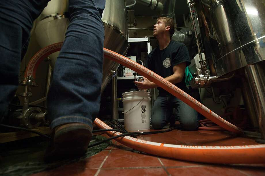 Bryce Tyranski, right, and Daniel Belloni clean the brewing tanks at Topsy's bar and lounge in San Francisco. Photo: Santiago Mejia, Special To The Chronicle