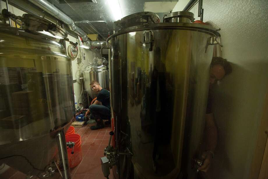 Bryce Tyranski (right) and Daniel Belloni clean the brewing tanks at Topsy's bar and lounge in San Francisco. Photo: Santiago Mejia, Special To The Chronicle