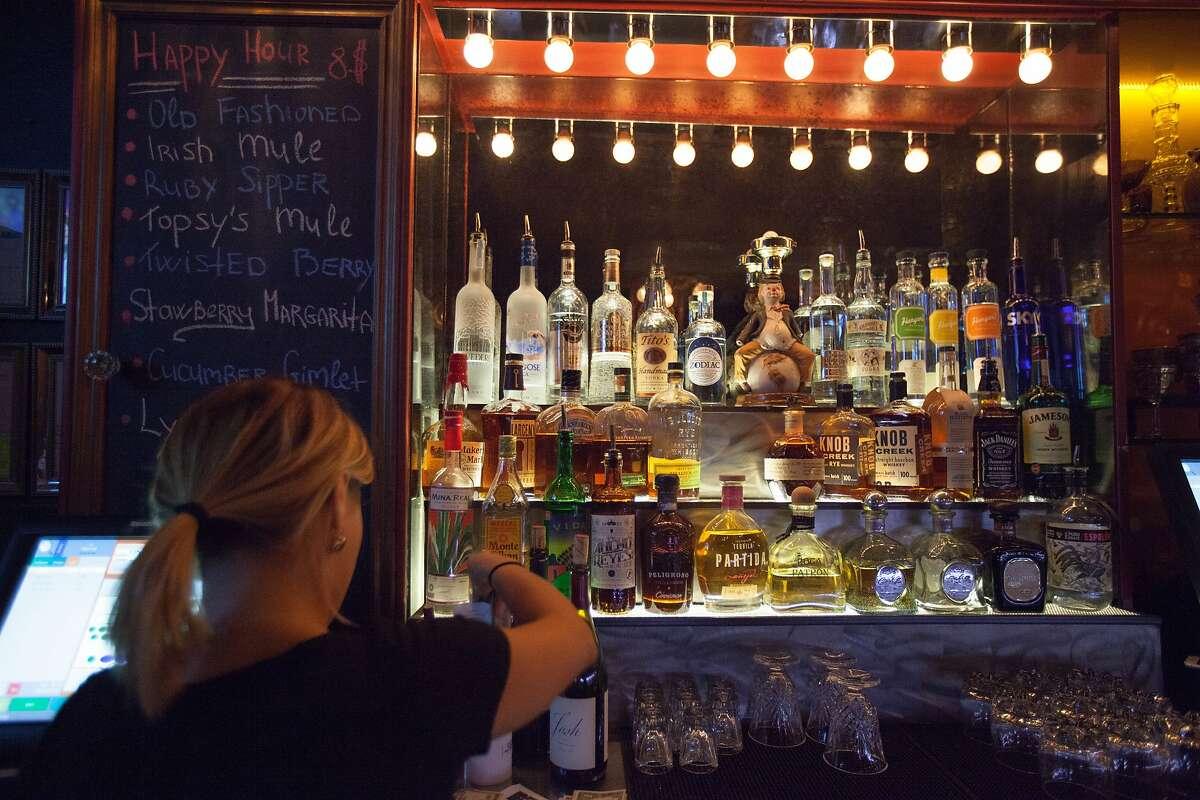 Bartender Adela Ciubara closes a guest's tab at Topsy's bar and lounge, Friday, Oct. 2, 2015, in San Francisco, Calif. The bar has a brewery downstairs and makes its own IPA.