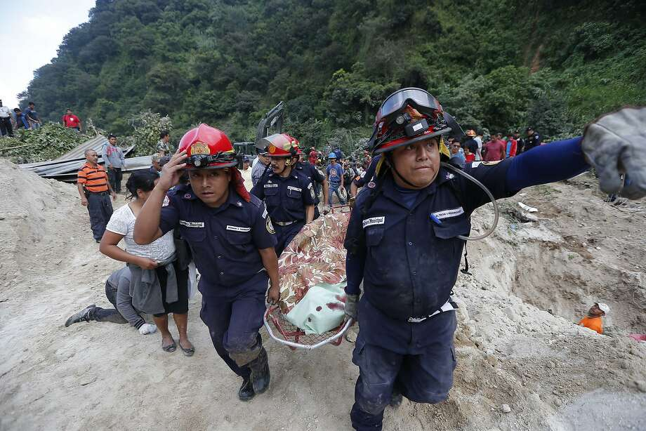 Rescue workers carry a body away from the site of Thursday's devastating mudslide in Santa Catarina Pinula, about 10 miles east of Guatemala City. Photo: Moises Castillo, Associated Press