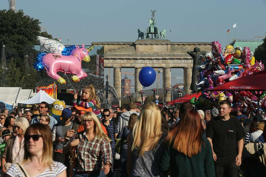 "A crowd gathers near the Brandenburg Gate in Berlin to celebrate the 25th anniversary of German reunification. ""Things worked out well,"" Chancellor Angela Merkel says. Photo: Sean Gallup, Getty Images"