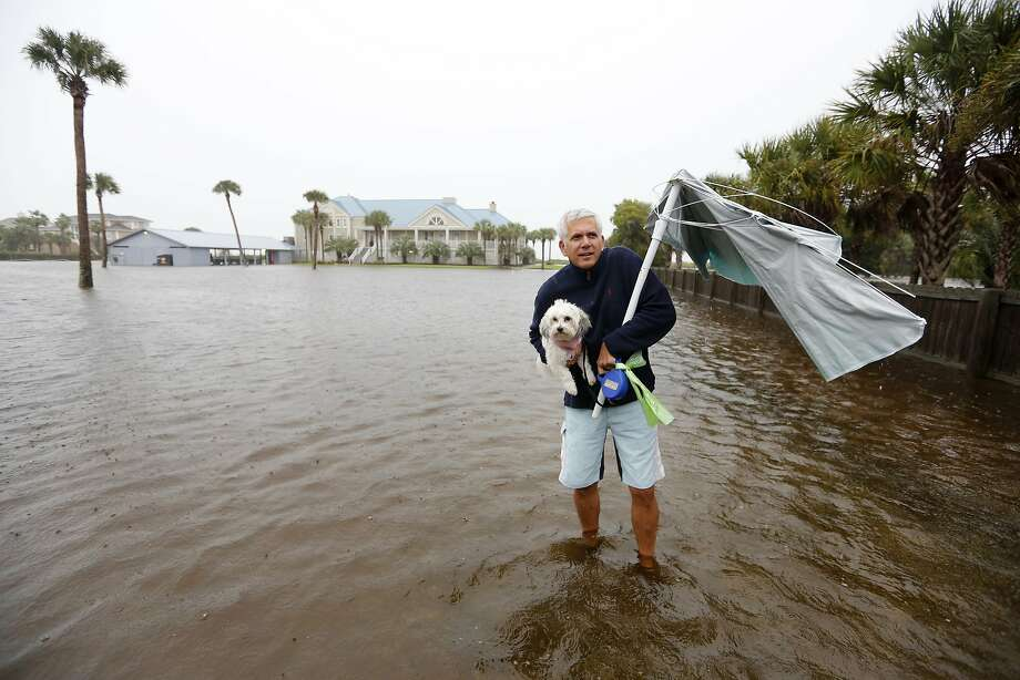 Randy Shirley sloshes across a flooded parking lot in Isle of Palms, S.C., while carrying his dog, Lulu. Photo: Mic Smith, Associated Press