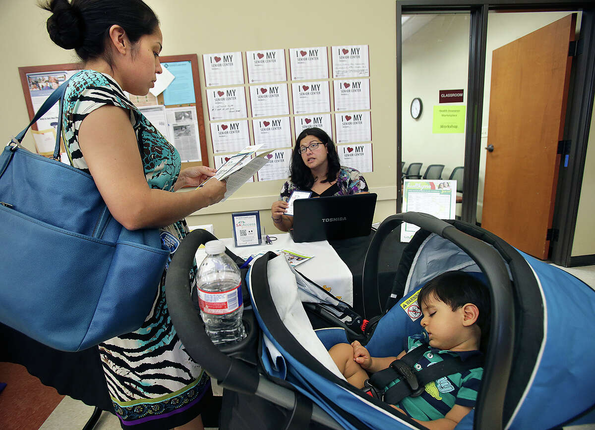 One year old Luca Hernandez is not too concerned while his mother, Vanessa Gomez, scouts out health care options as the San Antonio Eastside Promise Zone offers a Promise Zone to Health event with free health screenings for residents and their children on November 5, 2015. Gomez felt relieved to find an affordable health insurance plan in which she enrolled. Regina Maspero (back) with Health Collaborative offers her advice for additional services.