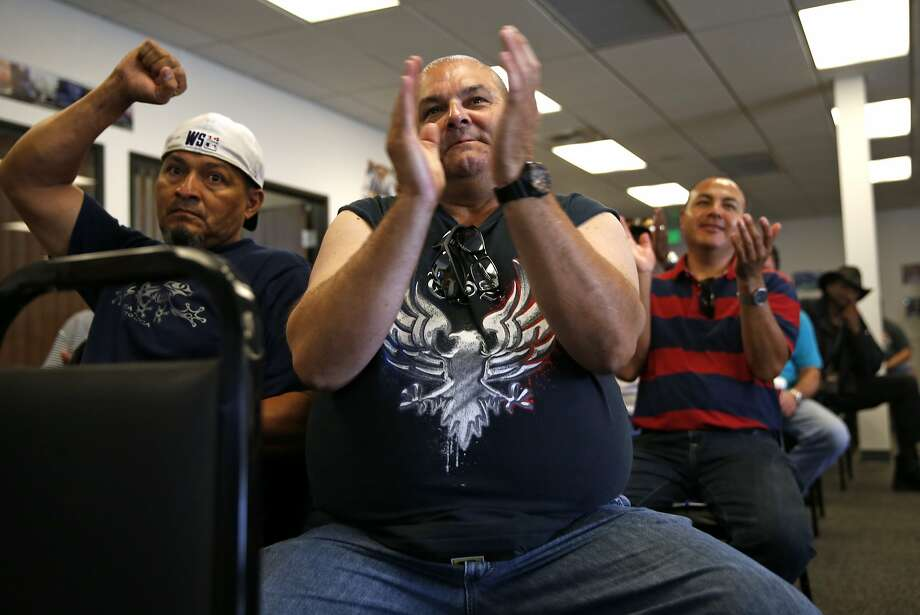 Genentech bus drivers Jose Quindinilla (left), Mark Zerrilla and Marco Marquez react during a Compass Transportation bus drivers meeting at Teamsters Local 853 in San Leandro, Calif., on Saturday, October 3, 2015. Photo: Scott Strazzante, The Chronicle
