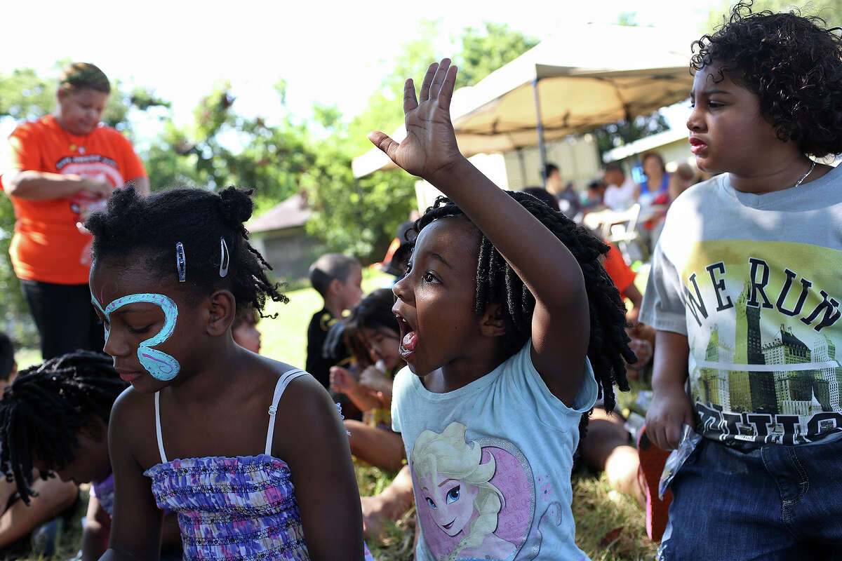Jordyn Lockett, 6, center, with Nevaeh Harris, 8, left, and Aron Mardi, 6, raises her hand for help as they participate in an activity to build a necklace during the monthly block party at H.I.S BridgeBuilders on Saturday, September 12, 2015.