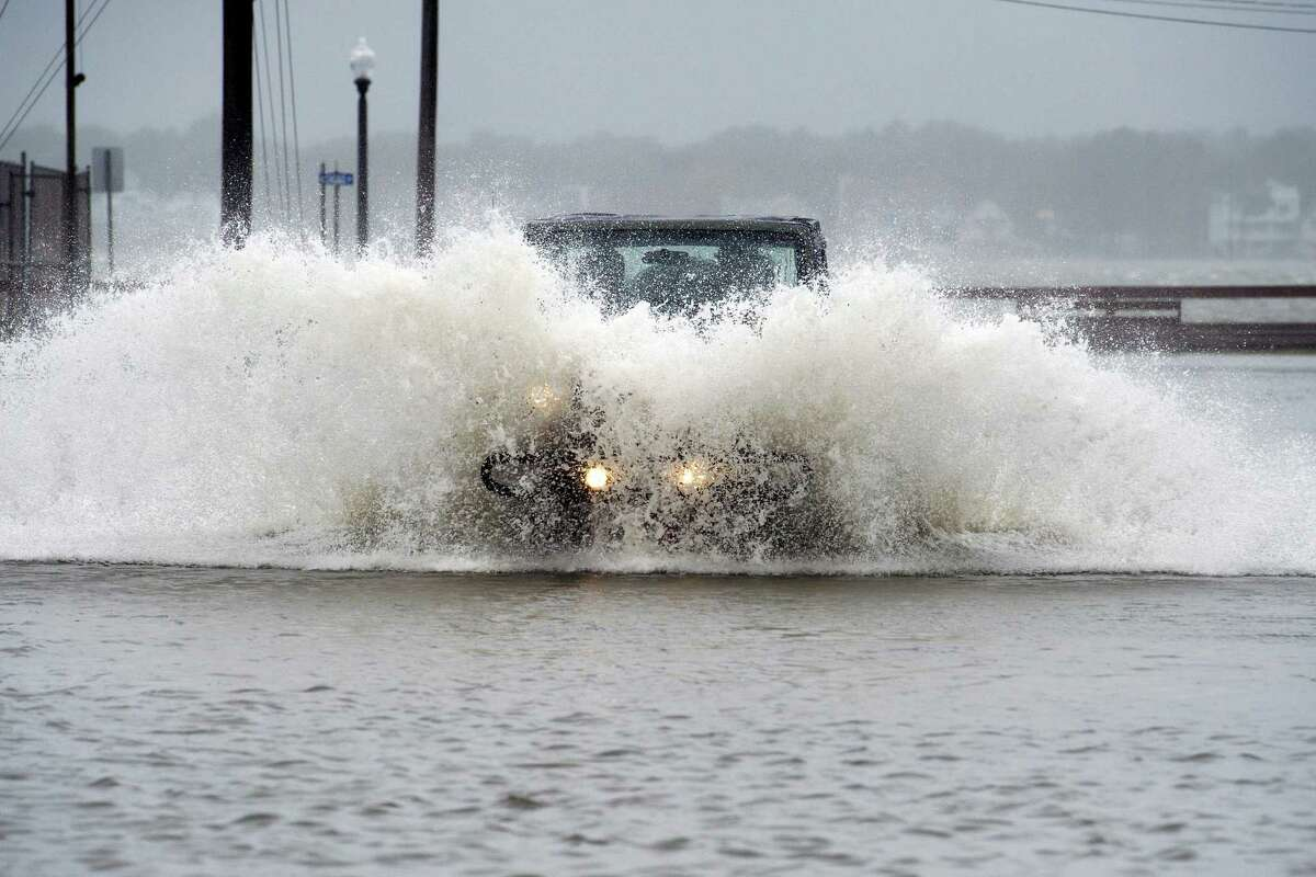 A Jeep plows through a flooded street in Ocean City, Md., Saturday. Rain pummeling parts of the East Coast showed little sign of slackening, with record-setting precipitation prolonging the soppy misery that has been eased only by news that Hurricane Joaquin will not hit the U.S.