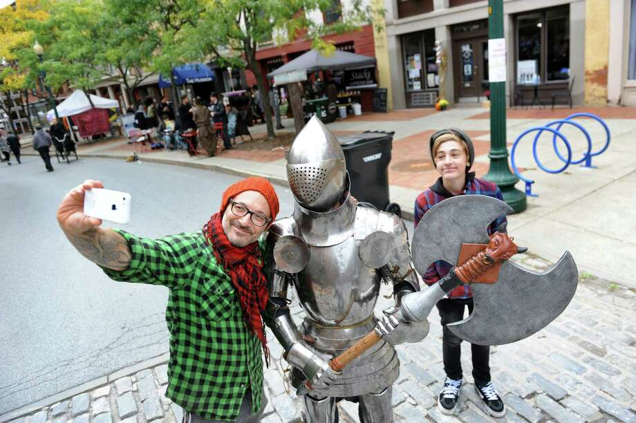 Jude Goldman of Saratoga Springs, left, and his son Mayfield Goldman, right, pose for a selfie with a knight in shining armor during the Enchanted City steampunk street festival on Saturday, Oct. 3, 2015, in Troy, N.Y. James Gillaspie of Albany was inside the protective suit that he made. The family-friendly event offered music, games, performance, food and fantasy. (Cindy Schultz / Times Union) Photo: Cindy Schultz / 10033593A