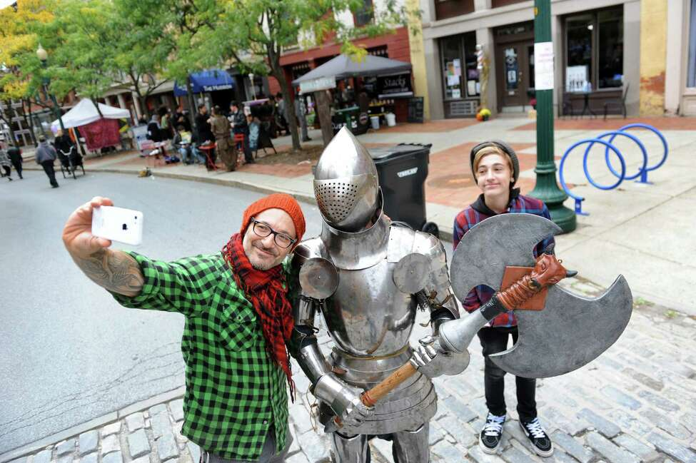 Jude Goldman of Saratoga Springs, left, and his son Mayfield Goldman, right, pose for a selfie with a knight in shining armor during the Enchanted City steampunk street festival on Saturday, Oct. 3, 2015, in Troy, N.Y. James Gillaspie of Albany was inside the protective suit that he made. The family-friendly event offered music, games, performance, food and fantasy. (Cindy Schultz / Times Union)