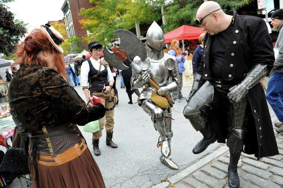 James Gillaspie of Albany, center, shows off his suit of armor as he mixes with others dressed up for the Enchanted City steampunk street festival on Saturday, Oct. 3, 2015, in Troy, N.Y. The family-friendly event offered music, games, performance, food and fantasy. (Cindy Schultz / Times Union) Photo: Cindy Schultz / 10033593A