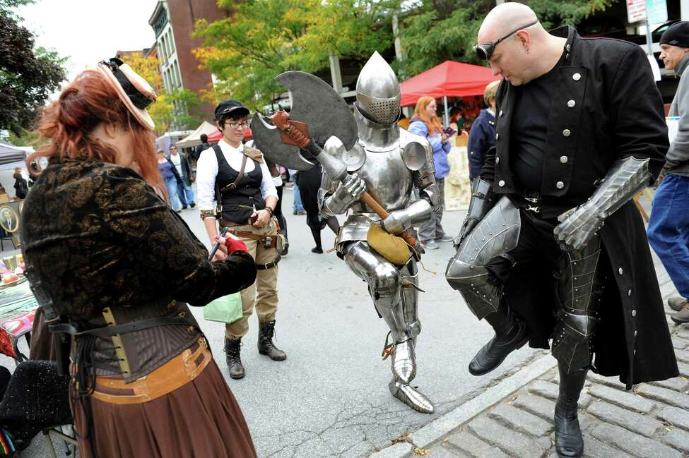 James Gillaspie of Albany, center, shows off his suit of armor as he mixes with others dressed up for the Enchanted City steampunk street festival on Saturday, Oct. 3, 2015, in Troy, N.Y. The family-friendly event offered music, games, performance, food and fantasy. (Cindy Schultz / Times Union)