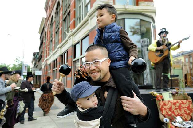 Huang Tran of Troy, center, dances with his two sons Jackson Tran, 4, top, and Hudson Tran, 1, during the Enchanted City steampunk street festival on Saturday, Oct. 3, 2015, in Troy, N.Y. The family-friendly event offered music, games, performance, food and fantasy. (Cindy Schultz / Times Union) Photo: Cindy Schultz / 10033593A