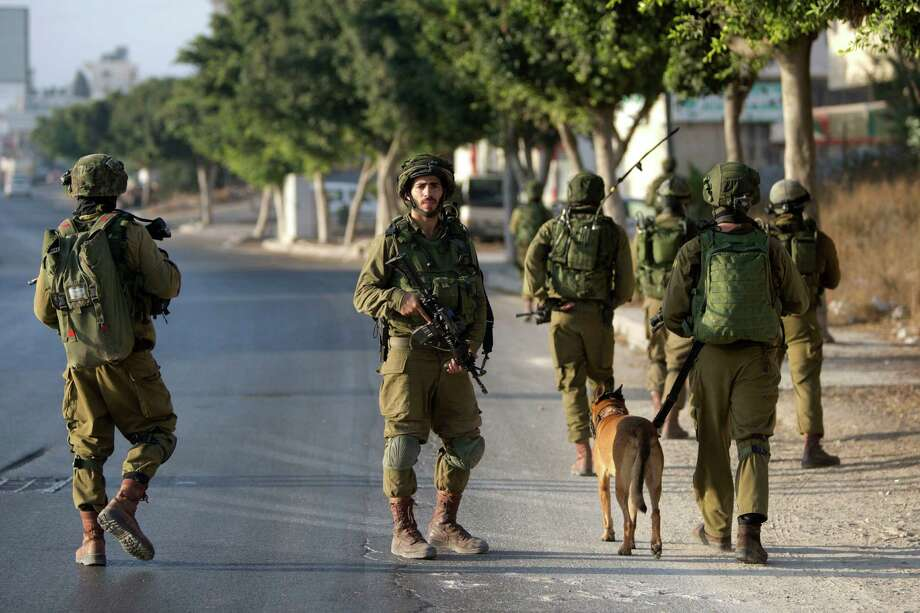 Israeli soldiers patrol during a search on Saturday for the suspected Palestinian killers of two Jewish settlers in the West Bank city of Nablus. An Israeli couple was killed in a drive-by shooting on a West Bank road Thursday.  Photo: Majdi Mohammed, STR / AP
