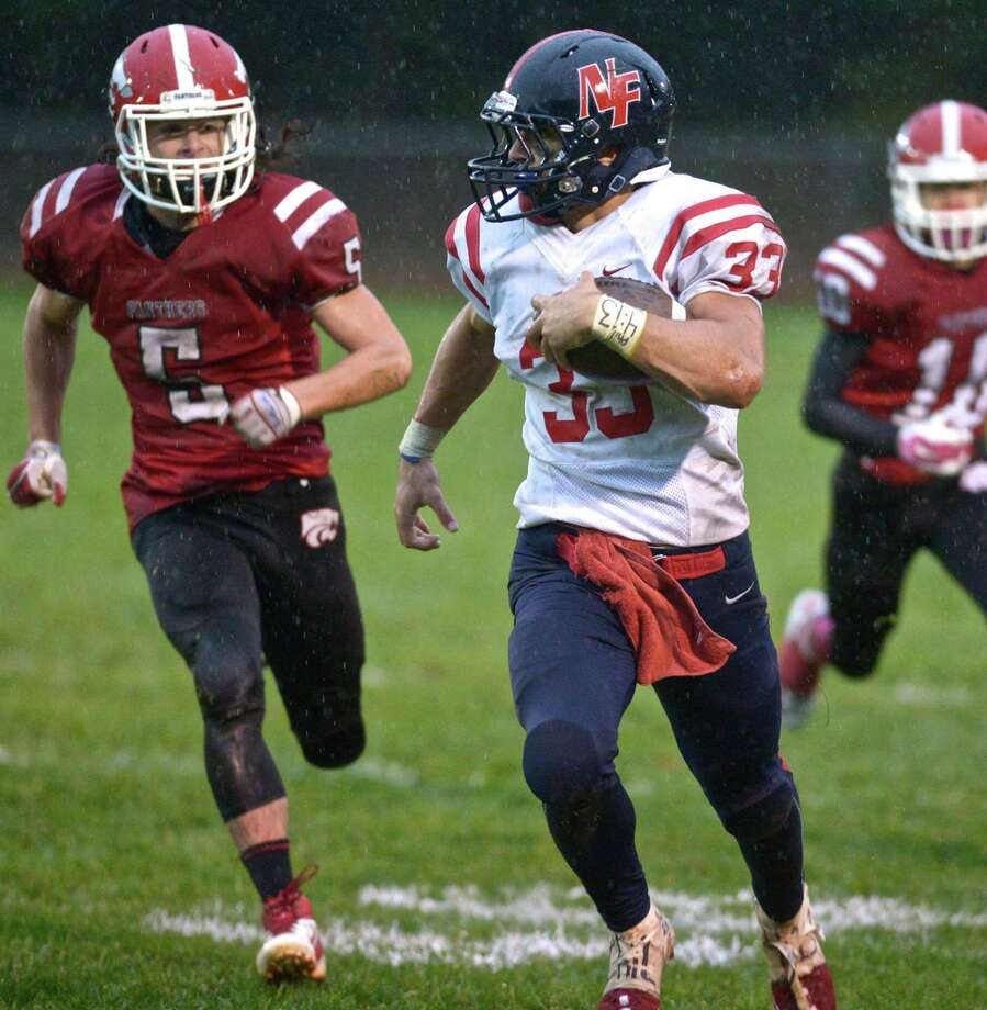 New Fairfield's Zachary Tripodi (33), who reversed field to turn a possible loss into a large gain, is pursued by Masuk's Jack Duigan (5) in the football game between New Fairfield and Masuk high schools on Friday, October 2, 2015, at Masuk High School, in Monroe, Conn. Photo: H John Voorhees III / Hearst Connecticut Media / The News-Times