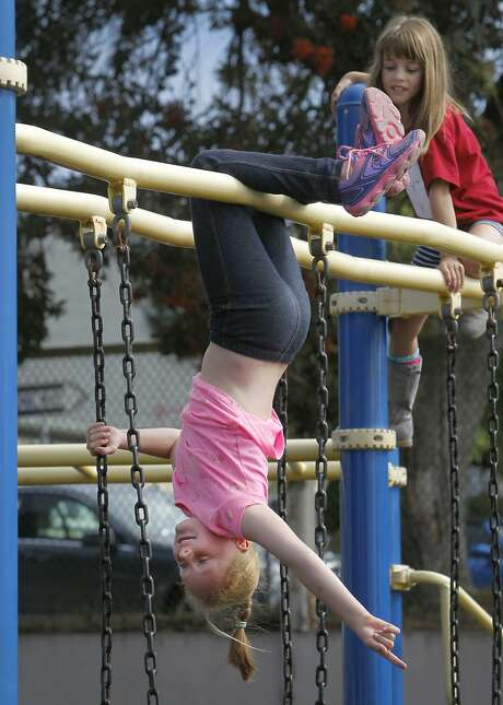 Second-grader Lilah Callahan hangs out with her friend Grace Wofsy (right) on a play structure at Commodore Sloat Elementary School. Photo: Paul Chinn, The Chronicle