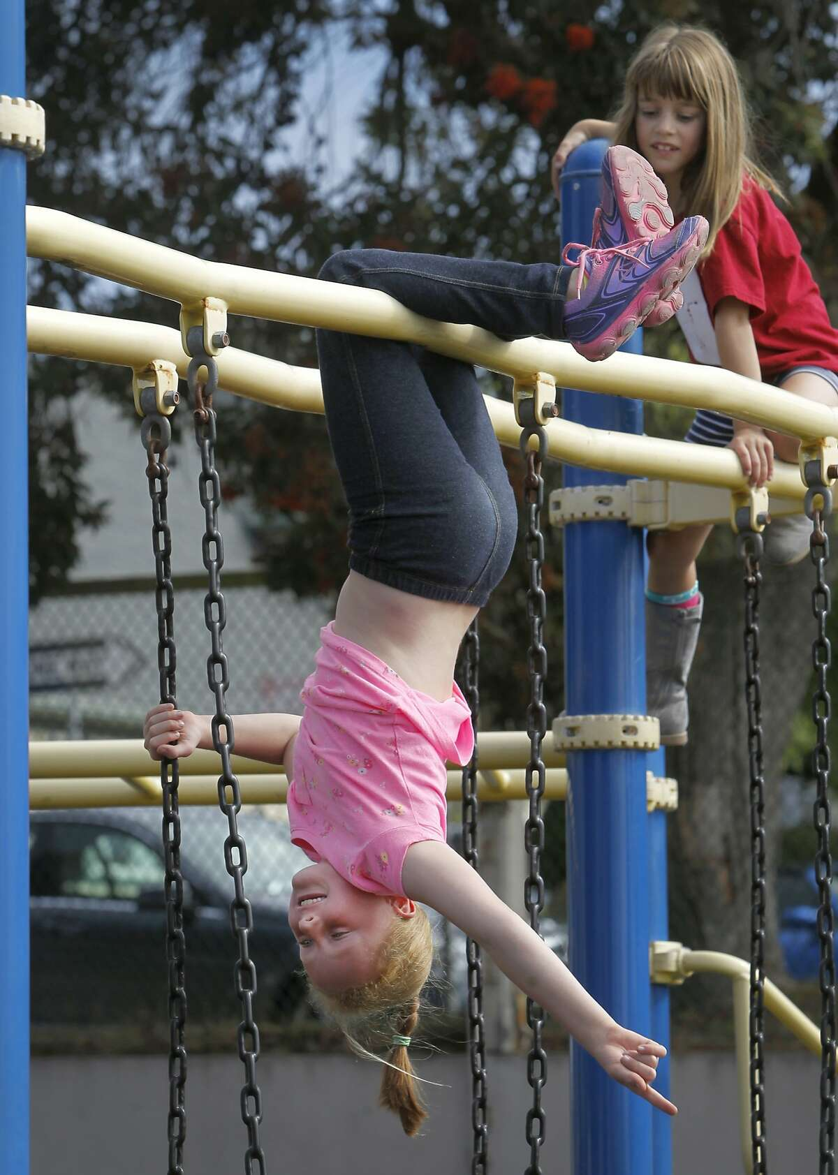 Second-grader Lilah Callahan hangs out with her friend Grace Wofsy (right) on a play structure at Commodore Sloat Elementary School in San Francisco, Calif. on Saturday, Oct. 3, 2015. The playground at the school joins a list of others citywide that will be open on weekends as part of the Shared Schoolyard project.