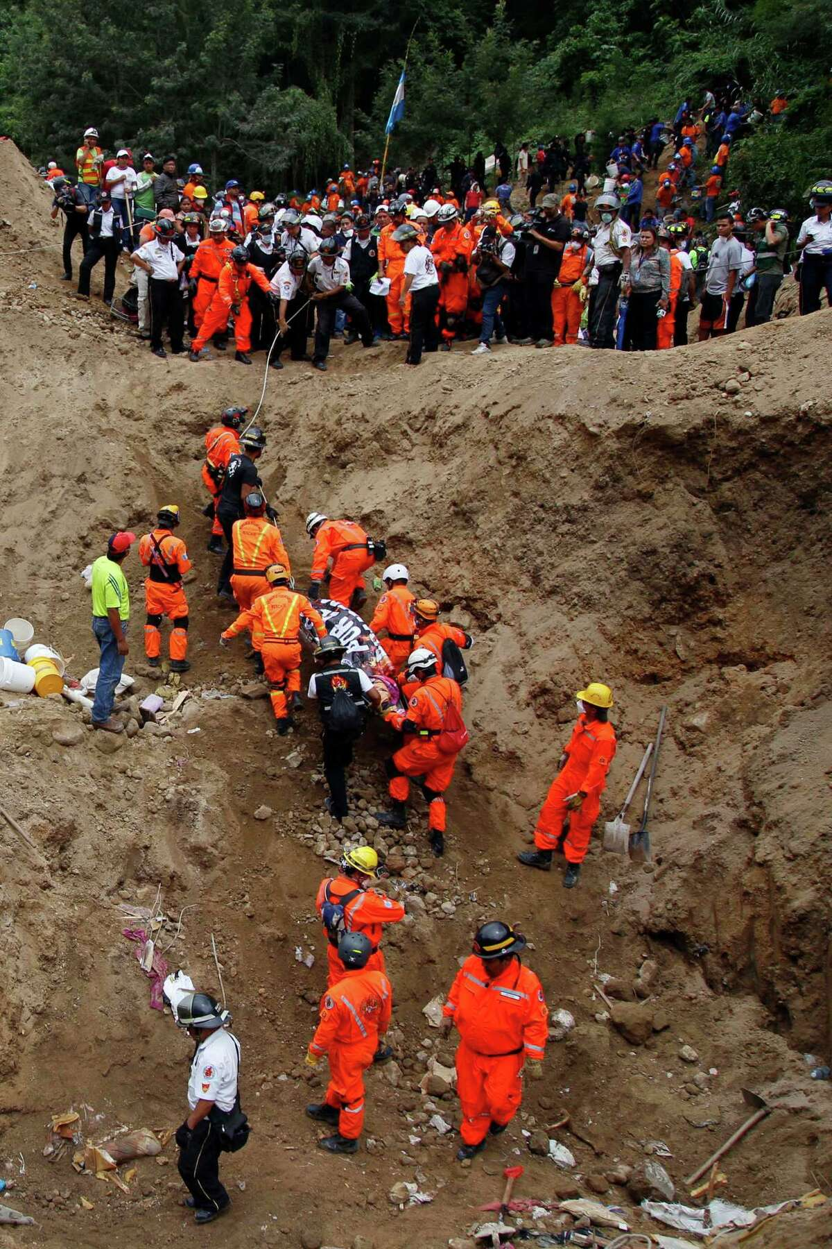Firemen and rescue workers carry a body from the site of a mudslide in Cambray, a neighborhood in the suburb of Santa Catarina Pinula, on the outskirts of Guatemala City, Saturday, Oct. 3, 2015. Rescue workers recovered more bodies Saturday after a hillside collapsed on homes late Thursday, while more are feared still buried in the rubble. (AP Photo/Luis Soto)