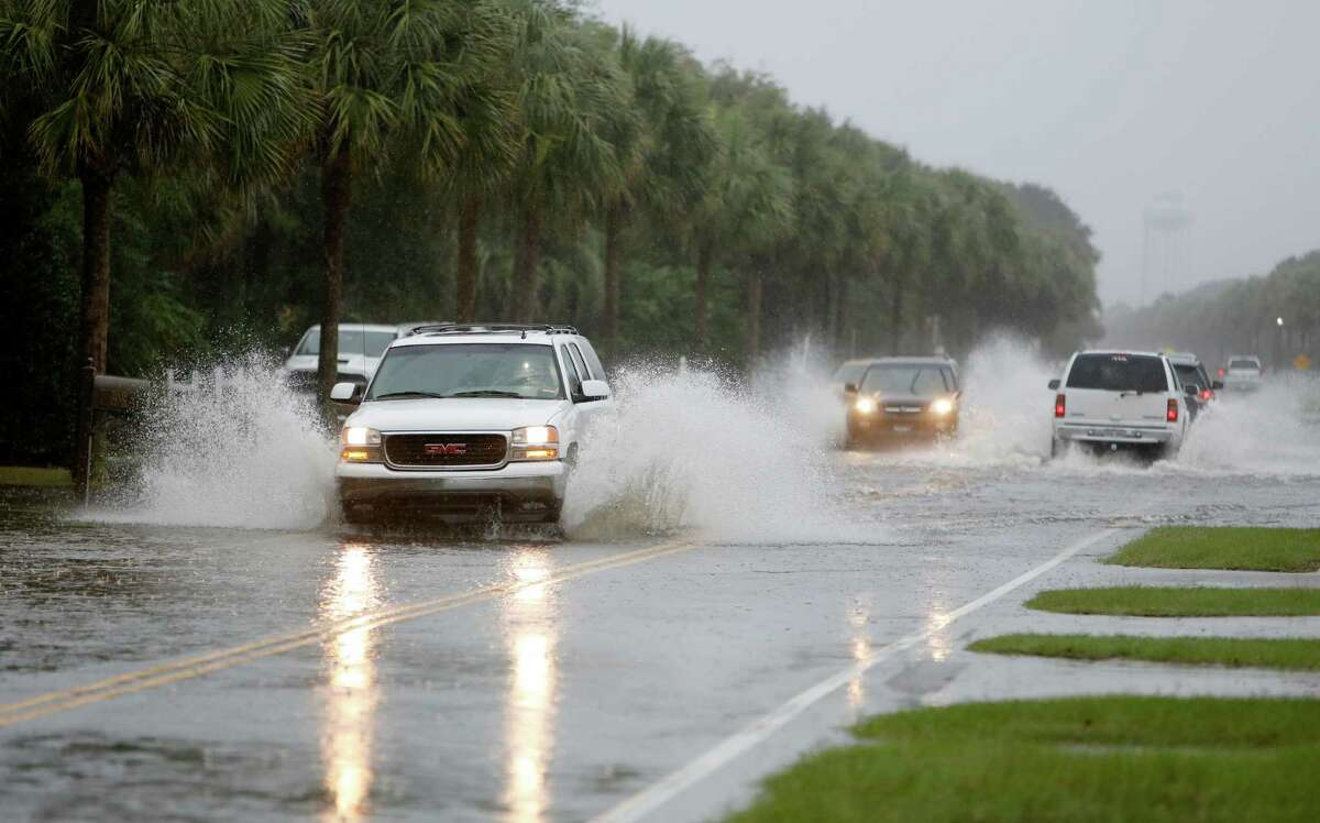 Cars make their way through Palm Blvd. on the Isle of Palms while the South Carolina coast is inundated with historic rain causing flooding Saturday, Oct. 3, 2015. The National Weather Service says the risk of flooding will continue through Monday morning, especially in parts of North and South Carolina that already have gotten up to 11 inches of rain this week. Forecasters say some areas could see storm totals as high as 15 inches. (AP Photo/Mic Smith) ORG XMIT: SCMS102