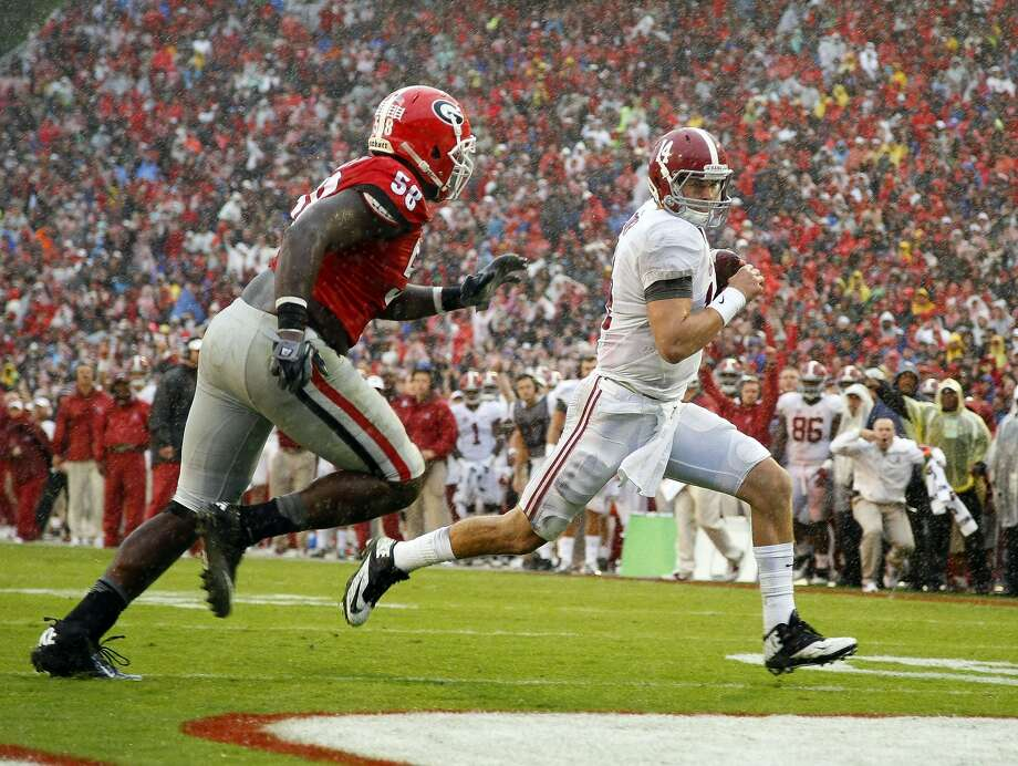 Alabama quarterback Jake Coker outruns Georgia defensive tackle Sterling Bailey to score a touchdown in the second half Saturday in Athens, Ga. Photo: Brett Davis, Associated Press