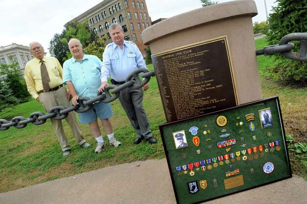 Dave Barnum, left, and John Mullen, right, both of the Rensselaer County Vietnam Veterans Memorial Committee, join Jim Quamo of Spencerport, center, on Tuesday, Sept. 29, 2015, at Riverfront Park in Troy, N.Y. Barnum and Mullen are working a campaign to have Quamo's brother, George Quamo, awarded a Medal of Honor. George Quamo, who's shadow box is at right, was a Green Beret soldier from Averill Park and led a heroic rescue mission in Vietnam. (Cindy Schultz / Times Union) Photo: Cindy Schultz / 00033511A