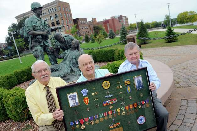 Dave Barnum, left, and John Mullen, right, both of the Rensselaer County Vietnam Veterans Memorial Committee, join Jim Quamo of Spencerport, center, on Tuesday, Sept. 29, 2015, at Riverfront Park in Troy, N.Y. Barnum and Mullen are working a campaign to have Quamo's brother, George Quamo, awarded a Medal of Honor. George Quamo, who's shadow box they hold, was a Green Beret soldier from Averill Park and led a heroic rescue mission in Vietnam. (Cindy Schultz / Times Union) Photo: Cindy Schultz / 00033511A