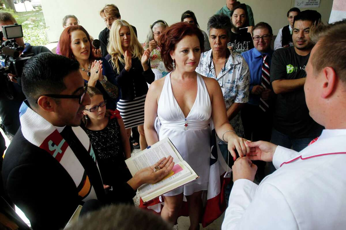 In this Wednesday, Sept. 18, 2013 file photo, Nikki Araguz, center, and William Loyd, right, are married by the Rev. Michael Diaz with Resurrection Metropolitan Community Church in Houston in front of the Nueces County Courthouse in Corpus Christi, Texas. The couple got married after Araguz's hearing in the Thirteenth Court of Appeals. Araguz, a transgender woman, is trying to collect benefits following the 2010 death of her former husband, Thomas Araguz, whose family argues that the marriage wasn't valid because Nikki Araguz was born a man. (AP Photo/Corpus Christi Caller-Times, Michael Zamora)