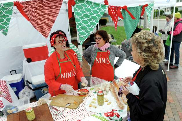 """Anita """"Nini"""" Nasuto of Guilderland, left, and her friend Kathy Breen, center, chat up customers as offer a taste of Nini's Sicilian Salsa during the Upper Union Street Harvest Fest and Art Show on Saturday, Oct. 3, 2015, in Schenectady, N.Y. (Cindy Schultz / Times Union) Photo: Cindy Schultz / 10033595A"""