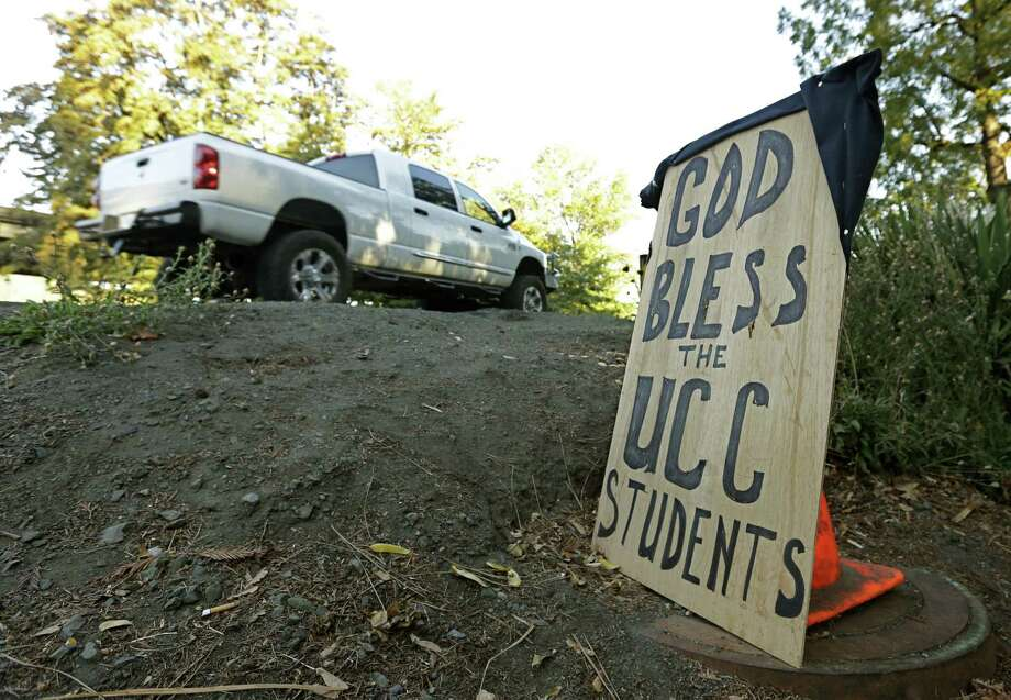 A sign honoring those killed in a fatal shooting at Umpqua Community College, is displayed Friday, Oct. 2, 2015, in Roseburg, Ore.  Armed with multiple guns, Chris Harper Mercer, walked into a class at the community college, Thursday, and opened fire, killing several and wounding others.  (AP Photo/Rich Pedroncelli) ORG XMIT: ORRP103 ORG XMIT: MER2015100213364845 Photo: Rich Pedroncelli / AP